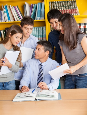college professor: Mature male teacher with books explaining students in college library
