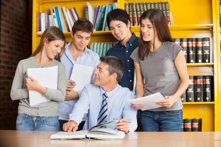 Happy college teacher pointing at book while discussing with students in library photo
