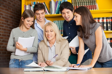 Happy university teacher with book explaining students in library photo