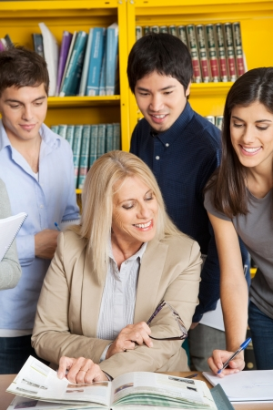 Happy female teacher discussing with students at table in college library photo