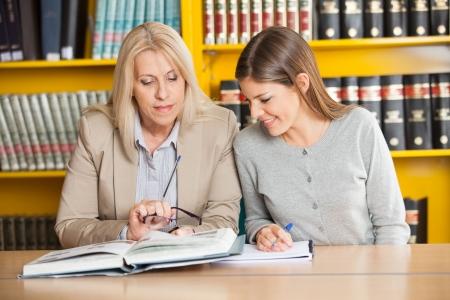 Mature female teacher explaining student in college library photo