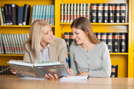 Happy university teacher holding book while explaining student in library photo