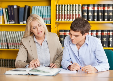 Mature female teacher explaining student while sitting at table in university library photo