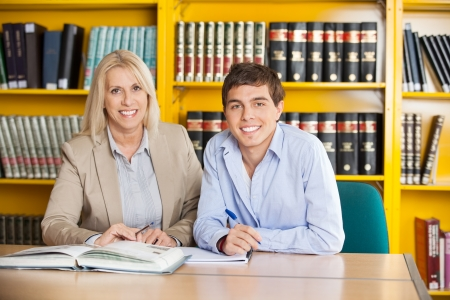 college professor: Portrait of confident male student and teacher with books sitting together at table in college library Stock Photo