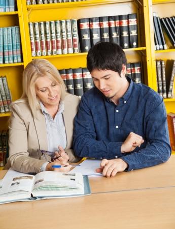 tutor: Profesora madura con los libros explicando los estudiantes en biblioteca universitaria