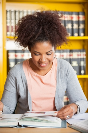 Young woman smiling while reading book at table in college library photo
