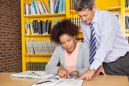 Mature male teacher explaining student at table in college library photo