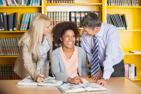 Cheerful college student with teachers in university library photo