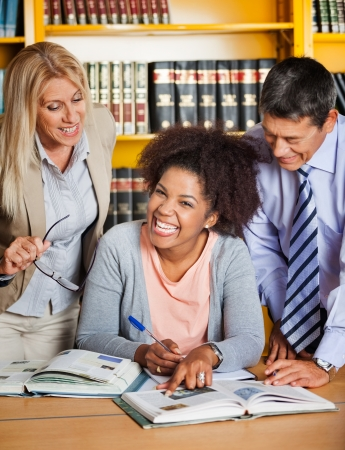 Portrait of cheerful female student with teachers standing besides her in college library photo