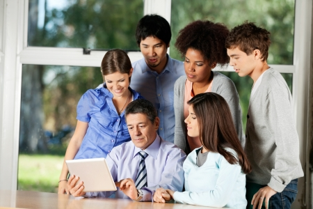 Mature male teacher using digital tablet while students standing around him in classroom photo