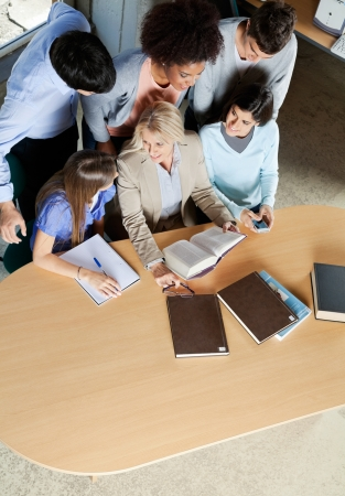 High angle view of mature teacher discussing with students at desk in classroom photo