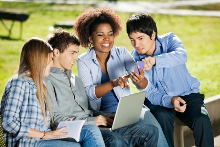 mobilephone: Happy young students with using mobilephone in university campus Stock Photo