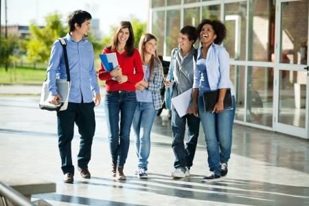campus building: Full length of cheerful university students walking on campus