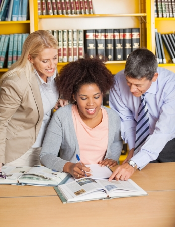 Happy mature teachers assisting student in college library photo
