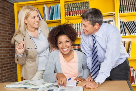 Portrait of cheerful female student with teachers looking at each other in university library photo
