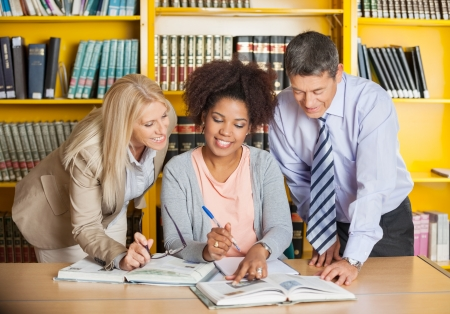Mature college teachers assisting student with studies in library photo
