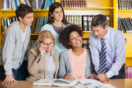 Mature teachers discussing with students in college library photo