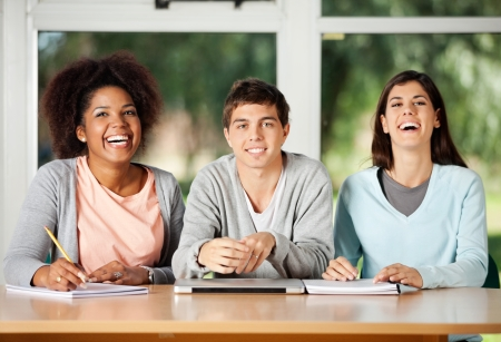 college classroom: Portrait of young male student with friends sitting at desk in classroom Stock Photo