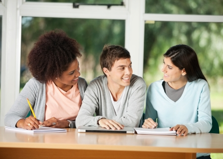 Young college students looking at female friend while sitting in classroom photo