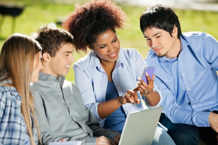 young adult: Young female student using mobilephone while classmates looking at it in campus
