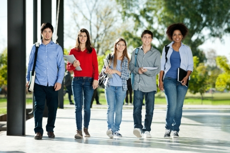 Full length portrait of confident students walking in a row on college campus