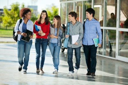 Full length of happy multiethnic students walking together on college campus photo