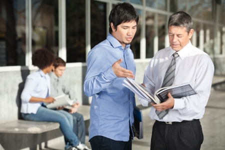 Mature male teacher holding books while discussing with student on college campus Stok Fotoğraf