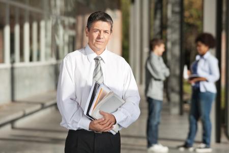 profesor: Retrato del profesor de sexo masculino confidente con los libros de pie en el campus universitario