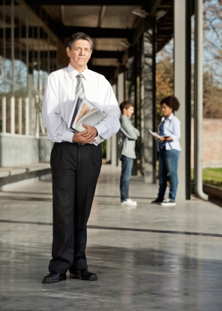 Full length portrait of mature male teacher with books standing on university campus photo