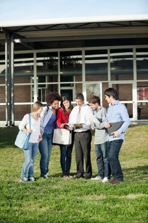 Full length of multiethnic students with teacher discussing over book on university campus photo