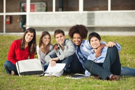 arms around: Portrait of happy multiethnic students sitting on grass at college campus