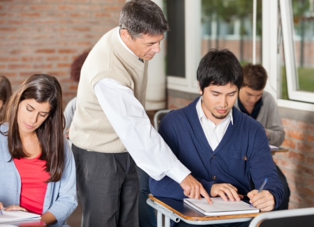 Mature male professor explaining test to student in classroom photo