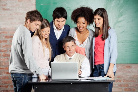 college professor: Mature male professor and students looking at laptop in classroom
