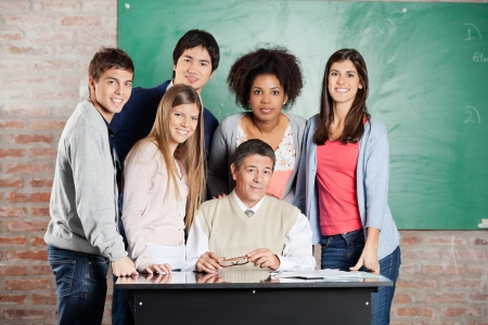 Portrait of confident male professor and students at desk against greenboard in classroom Stock Photo - 23746311