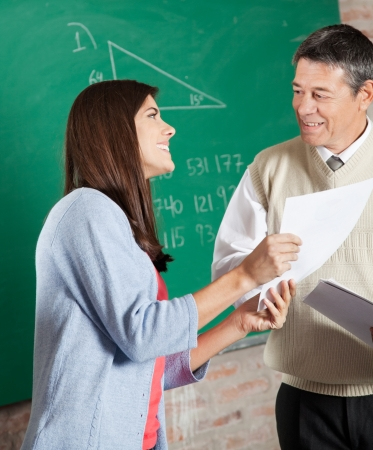 Happy female student with exam result looking at teacher in classroom Stock Photo - 23746310