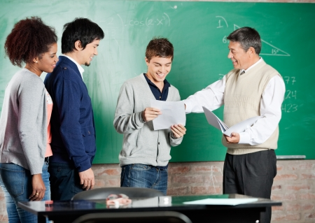 Happy male professor giving exam result to student with classmates standing in a row at classroom photo