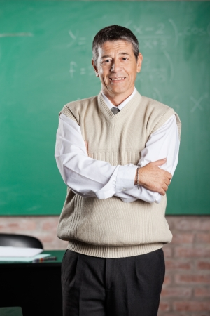 Portrait of confident male professor standing arms crossed in classroom photo