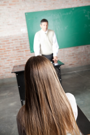 Rear view of female student with professor at desk in classroom photo