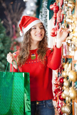 Happy woman in Santa hat with shopping bag buying Christmas ornaments at store photo