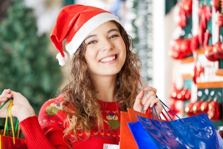 Portrait of happy woman in Santa hat carrying shopping bags at store photo