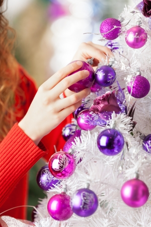 Cropped image of female owner hanging balls on Christmas tree at store photo