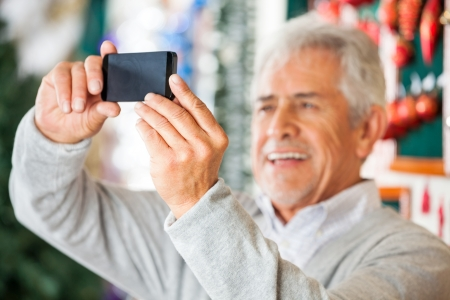 Happy senior man photographing through smartphone in Christmas store photo