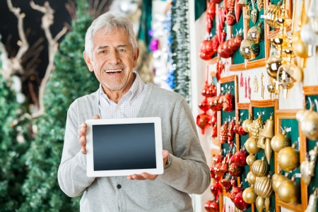 Portrait of happy senior man holding digital tablet while standing at Christmas store photo