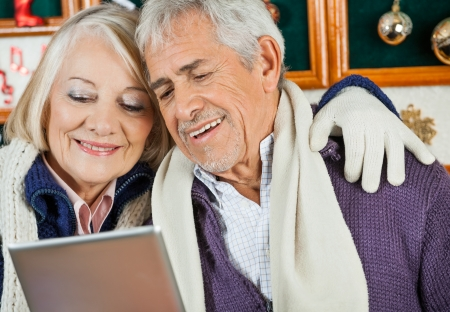 Happy senior couple using digital tablet together at Christmas store photo