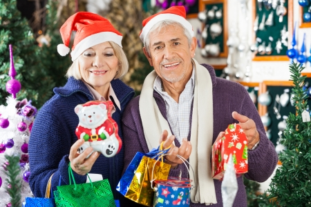 Portrait of happy senior man shopping for Christmas with woman in store photo