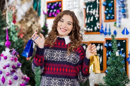 bureta: Retrato de una hermosa mujer joven sosteniendo peque�as bolsas de la compra en la tienda de la Navidad