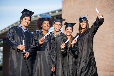 graduation gown: Portrait of happy multiethnic students in graduation gowns holding diplomas on university campus