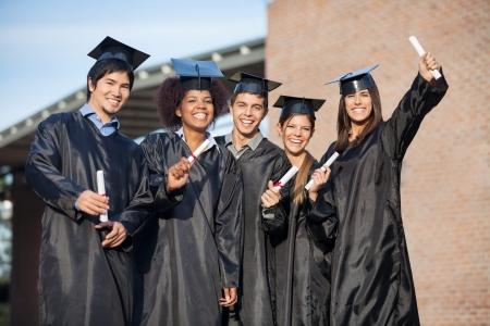 toga graduacion: Retrato de estudiantes felices multiétnicas en vestidos de graduación de la celebración de diplomas en el campus universitario Foto de archivo