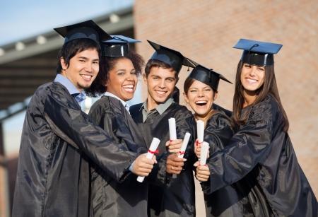 graduacion de universidad: Retrato de estudiantes felices en vestidos de graduación que muestran diplomas en el campus universitario