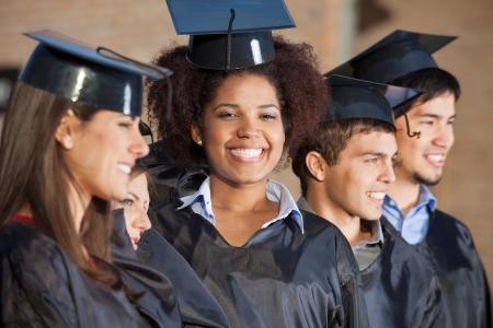 graduacion de universidad: Retrato de mujer joven y feliz con sus amigos en una fila en el día de la graduación en la universidad Foto de archivo